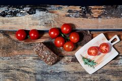 Bright red ripe tomatoes on branch covered with water drops composed on wood planks.  royalty free stock image