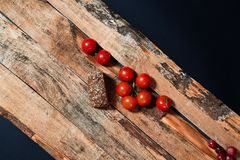 Bright red ripe tomatoes on branch covered with water drops composed on wood planks.  stock photos
