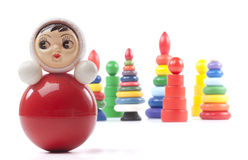 Bright red roly-poly toy. And many pyramidions Stock Images