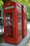 Bright red shiny telephone box. stock images