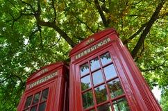 Bright red shiny telephone box. royalty free stock photography