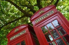 Bright red shiny telephone box. stock photo