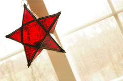Bright red star ornament. High-key photo of a bright red star ornament hanging on a window with backlighting. copy space Stock Photography