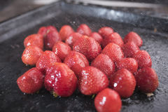 Bright red strawberry under the spray of drops of water Royalty Free Stock Images