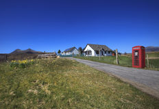 A bright red telephone booth in Scottish Highlands. A bright red telephone booth in small village in  Highlands, Scotland. Whenever you go you can find old Stock Photography