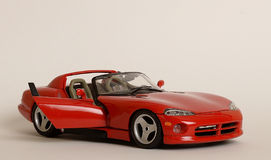 Bright Red Toy Sports Car. Bright red toy car with open door on white background. Dodge Viper Royalty Free Stock Photos