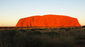 Bright red uluru at sunset stock video footage