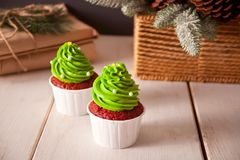 Bright red velvet cupcakes in the form of Christmas trees on a white wooden background stock photo