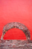 Bright Red Wall and Brick detail. Bright red wall with old worn brick detail Stock Photo