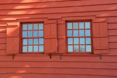 Bright red wall of home with wood siding and two shuttered windows Royalty Free Stock Image