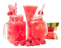 Watermelon smoothie in a mason jar decorated with a slice of watermelon, raspberries and ice cubes isolated on white background. f royalty free stock photo