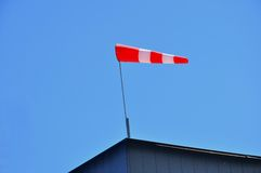 A bright red windsock atop a building Stock Photography