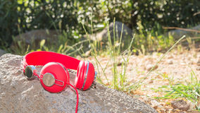 Bright red wired headphones on the rock Royalty Free Stock Photography