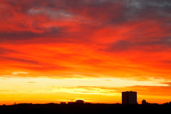 Bright red, yellow, blue clouds in sunrise sky Royalty Free Stock Image
