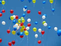 Bright red, yellow, blue, and white balloons released into a blue sky. Royalty Free Stock Image