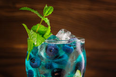 Bright refreshing blue lagoon cocktail with mint, ice cubes, bilberries on the wooden background. Summer beverages. Stock Images