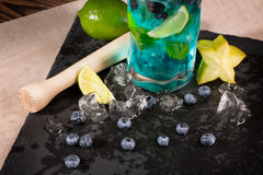 Bright refreshing blue lagoon cocktail with slices of lime, ice, bilberries and carambola, on  the black table-napkin. Royalty Free Stock Photos