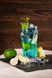 Bright refreshing blue lagoon cocktail with slices of lime, mint, ice, bilberries and carambola, on the table. Copy space. Stock Photography