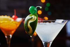 Bright refreshing cocktails: lime daiquiri on a table in a restaurant with creative decoration of lime slices and ice on a wooden Royalty Free Stock Photo