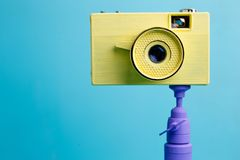 Bright retro vintage camera on tripod on blue background, close. Up. Photography concept Royalty Free Stock Photography