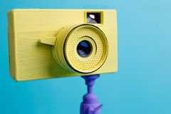 Bright retro vintage camera on tripod on blue background, close. Up. Photography concept Stock Images