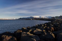 Bright Reykjavik against the backdrop of zasnezhenyh mountain peaks stock photography