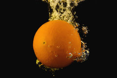 Bright ripe orange dropping into water as it breaks the surface Stock Photography