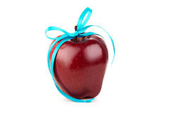 Bright ripe red apple and blue ribbon. On a white background Stock Photography