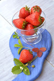 Bright and ripe strawberry in glass dish - sweet dessert in summer. Bright and ripe strawberry in glass dish on white background - sweet, healthy dessert in Stock Images