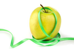 Bright ripe yellow apple and green ribbon. Bright ripe apple and green ribbon on a white background Royalty Free Stock Photos