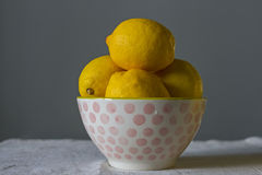 Bright ripe yellow lemons in a white porcelain bowl with pink balls in drops of water on a baggy cloth on a gray background. Royalty Free Stock Image