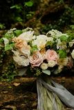 Bright romantic bouquet of flowers with ribbons on the background of the garden. fine art style. Bright romantic bouquet of flowers with ribbons on a light stock images