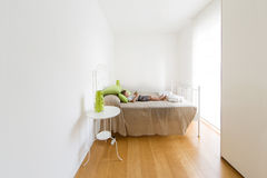 Bright room, bed and young child with tablet Stock Photos