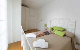 Bright room, bed and young child with tablet Royalty Free Stock Photos