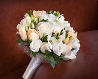 Bright roses wedding bouquet on brown leather sofa. Bright roses wedding bouquet on the brown leather sofa Royalty Free Stock Photos