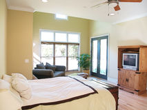 Bright Rustic Bedroom. A brightly lit rustic bedroom in a modern american home with a television, loveseat, trunk, and large windows overlooking the yard Royalty Free Stock Images