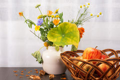 Bright rustic bouquet of flowers, apples in a wicker bowl Stock Photos