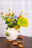Bright rustic bouquet of withering flowers in a ceramic vase Stock Image