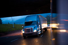 Bright semi truck in raining night lights on highway. Blue semi truck in the reflection of the evening headlights lights of car on a wet raining evening road Royalty Free Stock Photography