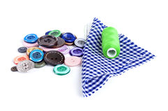 Bright sewing buttons, needle and skeins of thread Royalty Free Stock Photography