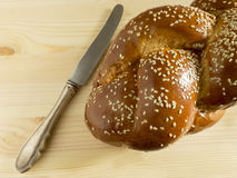Bright Shabbat challah. And knife on wooden background Royalty Free Stock Photography