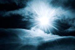 Bright shine through night sky with clouds. Blue tint Stock Photos