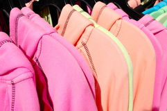 Bright Shirts. A row of brightly colored shirts hanging on hangers for sale at the outdoor market royalty free stock image
