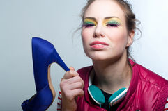 Bright shoe girl. Studio portrait on gray of young beautiful fashion girl wearing colorful makeup with purple long eyelashes, green earphones, pink vest, holding Stock Images