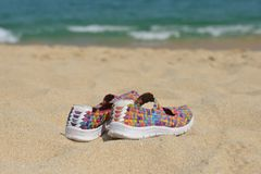 Bright shoes on the beach. royalty free stock photography