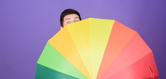 A bright sight against the backdrop of a rainy day. Gay with open umbrella. Homosexual man holding colorful umbrella. Fashion man with colorful rain gear. The royalty free stock photos