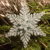 Bright silver six point star decoration on christmas tree Stock Photo