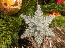 Bright silver six point star decoration on christmas tree Royalty Free Stock Photos