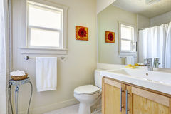 Bright simple bathroom. Interior with light wooden cabinet and large mirror Stock Photo