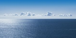 Bright sky with small clouds suspended in the sky over a calm sea in French Riviera France royalty free stock photo